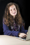Sentada adolescente en la tabla con un ordenador portátil Foto de archivo