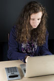 Sentada adolescente en la tabla con un ordenador portátil Fotografía de archivo