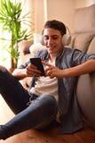 Sentada adolescente en piso usando una vertical del smartphone en casa Imagen de archivo