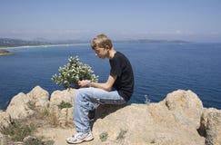 Sentada adolescente en rocas Foto de archivo libre de regalías