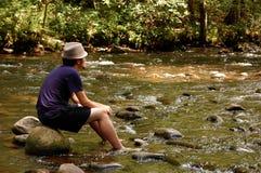 Sentada adolescente en rocas del río Fotografía de archivo