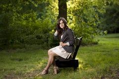 Sentada adolescente hermosa en un banco en parque Fotografía de archivo