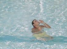 Sentada adolescente joven en el océano claro azul y codicioso consumición de su cokctail Imagen de archivo libre de regalías