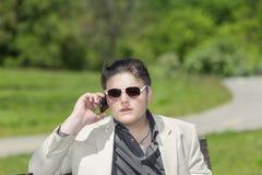 Sentada adolescente joven en parque en día caliente soleado brillante y hablar en el teléfono móvil Imágenes de archivo libres de regalías