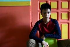 Sentada adolescente joven en una silla contra una pared colorida Fotografía de archivo libre de regalías