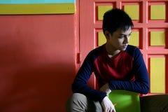 Sentada adolescente joven en una silla contra una pared colorida Fotografía de archivo