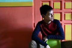 Sentada adolescente joven en una silla contra una pared colorida Fotos de archivo libres de regalías