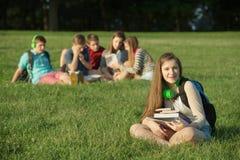 Sentada adolescente linda cerca del grupo Imágenes de archivo libres de regalías
