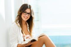 Sentada adolescente linda con el libro en la ventana. Fotografía de archivo libre de regalías