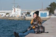 Sentada adolescente rizada dulce al borde del puerto Fotografía de archivo