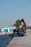 Sentada adolescente rizada dulce al borde del puerto Foto de archivo