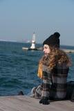 Sentada adolescente rizada dulce al borde del puerto Fotos de archivo