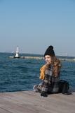 Sentada adolescente rizada dulce al borde del puerto Fotos de archivo libres de regalías