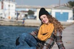 Sentada adolescente rizada dulce al borde del puerto Imagenes de archivo