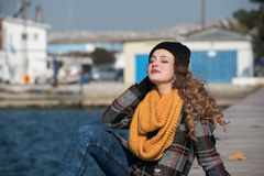 Sentada adolescente rizada dulce al borde del puerto Fotografía de archivo libre de regalías
