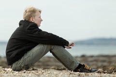 Sentada adolescente rubia tranquila en la playa rocosa Fotografía de archivo libre de regalías