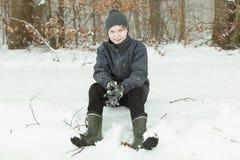 Sentada adolescente sonriente en la nieve cerca del bosque Imágenes de archivo libres de regalías