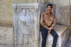 Sentada adulta iraní en el banco de piedra cerca del bajorrelieve de la calle Imagen de archivo