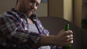 Sentada alcohólica adulta en el sofá y el hablar con la botella de cerveza, degradación almacen de metraje de vídeo