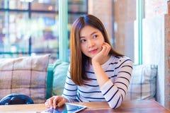 Sentada asiática atractiva joven feliz de la mujer y relajación por el w fotografía de archivo libre de regalías