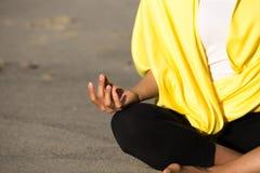 Sentada asiática en la arena que medita amarillo que lleva Foto de archivo