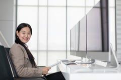 Sentada asiática joven hermosa en oficina moderna feliz, allí a imagenes de archivo