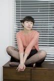 Sentada atractiva joven de la mujer Fotos de archivo