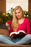 Sentada cómoda de la mujer en el sofá, el libro de lectura y el té de consumición fotografía de archivo