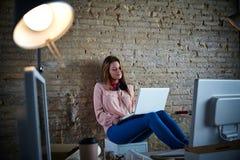 Sentada casual de la empresaria en la oficina con el ordenador portátil Imágenes de archivo libres de regalías