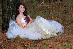 Sentada de la biblia de la chica joven Foto de archivo libre de regalías
