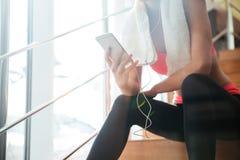 Sentada de la deportista y smartphone con con los auriculares en gimnasio imagenes de archivo