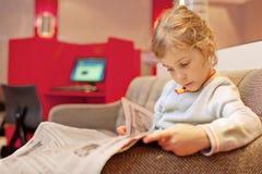 sentada de la muchacha y periódico leído Imágenes de archivo libres de regalías