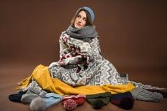 Sentada de la mujer envuelta en mantas foto de archivo