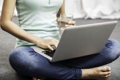Sentada de la mujer joven mientras que usa el ordenador portátil Imágenes de archivo libres de regalías
