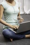 Sentada de la mujer joven mientras que usa el ordenador portátil Imagen de archivo
