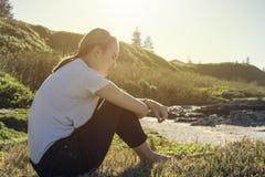 Sentada de la mujer joven y relajación en sol de la mañana imágenes de archivo libres de regalías