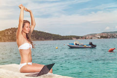 Sentada de la mujer y relajación en una playa con un ordenador portátil fotos de archivo libres de regalías