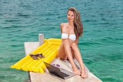 Sentada de la mujer y relajación en una playa con un ordenador portátil imagenes de archivo