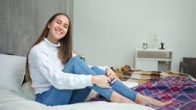 Sentada de risa encantada de la mujer descalza bonita joven en cama en el dormitorio que disfruta de fin de semana almacen de video