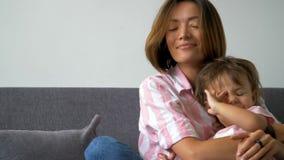 Sentada de risa joven de la madre y de la hija de la familia cariñosa hermosa feliz en el sofá metrajes