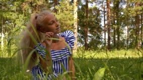 Sentada de sueño y de pensamiento de la muchacha adolescente pensativa en el claro en parque de naturaleza almacen de video