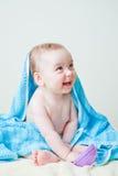 Sentada del bebé cubierta por el juguete azul de la explotación agrícola de la toalla Imágenes de archivo libres de regalías