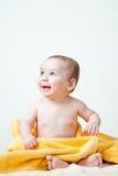 Sentada del bebé envuelta en toalla amarilla Imagen de archivo