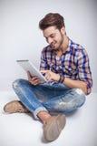 Sentada del hombre de la moda de los jóvenes mientras que usa una tableta Foto de archivo libre de regalías