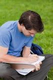 Sentada del hombre joven mientras que escribe en su cuaderno Imagenes de archivo