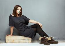 Sentada del modelo de manera Muchacha hermosa en alineada negra Imagen de archivo libre de regalías