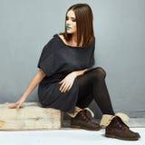 Sentada del modelo de manera Muchacha hermosa en alineada negra Foto de archivo libre de regalías