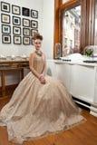 Sentada del vestido del diseño de la muchacha Fotografía de archivo