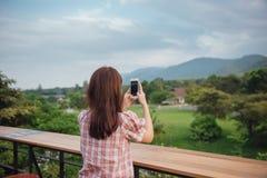 Sentada del viajero de la mujer joven y relajación en el café al aire libre que toma la foto con el teléfono elegante en la monta imagen de archivo