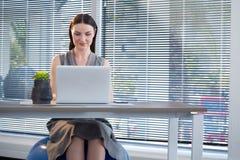 Sentada ejecutiva femenina en bola del ejercicio mientras que trabaja en el escritorio foto de archivo